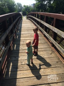 Just two brothers walking over a bridge.